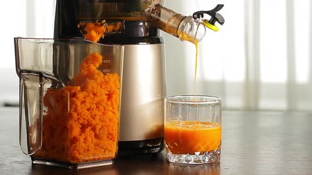 havuç : Fresh carrot juice pours of juicers in a glass on the table. Stok Video