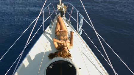 żaglówka : Beautiful girl sunbathing on the yacht. Rest on a yacht. Holiday on the islands. Seascape.