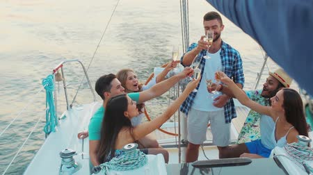 żaglówka : Young people is resting on the sailing yacht. Corporate party on a yacht. Friends spend a weekend on a yacht. Event on the yacht. Merry company is celebrating a birthday on a yacht.