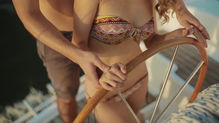 yatçılık : Helm of yacht. The steering wheel of the yacht. Yachting. Guy teaches the girl of yachting. Guy and girl hands on the wheel. Love story. Lovers on a yacht.