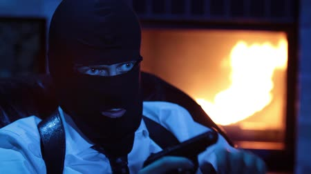 hostility : Man in the mask recharge the gun. Terrorist blackmail the victim. Thug in balaclava with gun. Gangster with weapons. Stock Footage