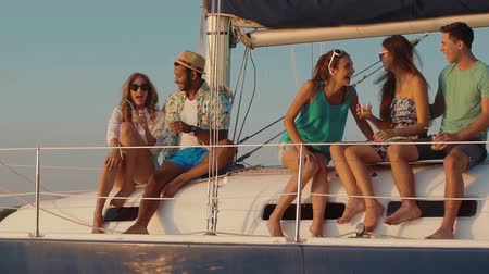 żaglówka : Young people relaxing on a yacht. Party on a yacht. Corporate party on a yacht. Young people having fun on a yacht. Walk on a yacht along the river. Cruise on a boat.