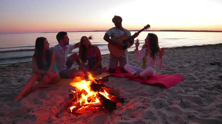 juventude : Young people dance and sing on the beach. Camping on the island. Youth with a guitar singing songs. Friendly company meets the dawn. Youth recreation in nature.