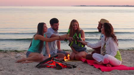 şenlik ateşi : Company of cheerful friends meet a dawn on the seashore. Young people drinking beer on vacation. Young guys and girls drink near the campfire. Stok Video