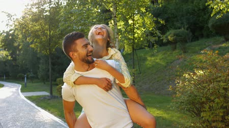sucesso : Guy and a girl having fun in the park. Lovers enjoy each other. Romantic date in a beautiful park.