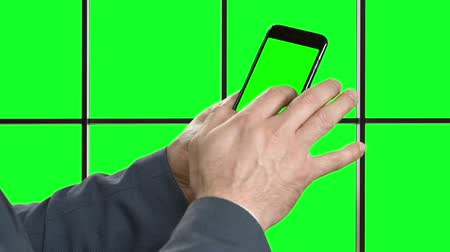 chrom : Businessman uses the Internet on phone. Internet in smartphone. Mans hand with phone on a green background. Alpha Channels.