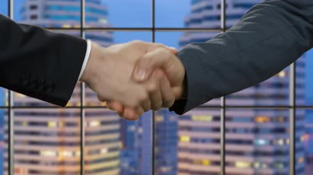 promover : Businessmen shake hands at night time.