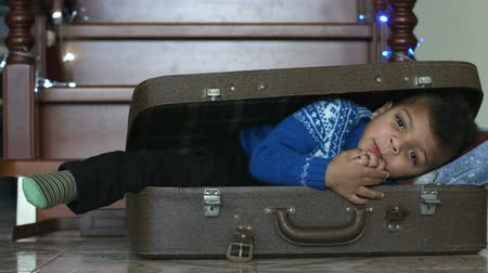 darkskinned : Cute afro boy inside suitcase.