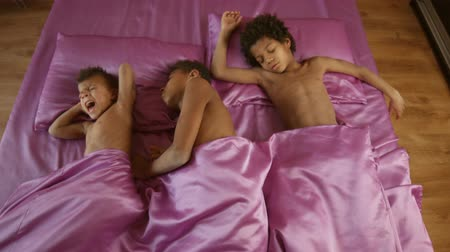 darkskinned : Three afro kids sleeping together.