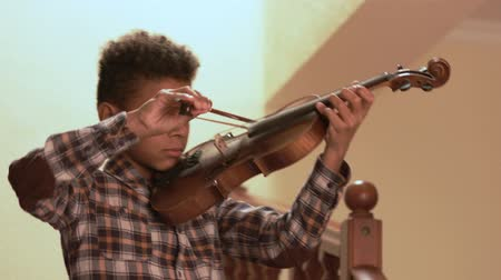 sonata : Smiling afro kid plays on violin.
