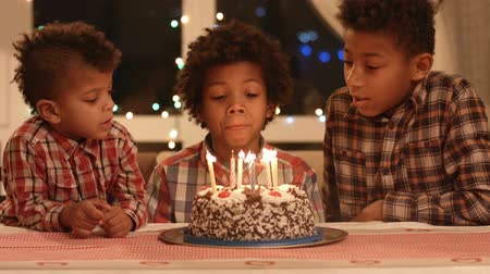darkskinned : Boy blows out the candles and make a wish.
