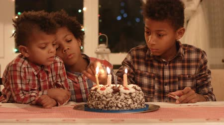 darkskinned : Kids lighting birthday cakes candles.