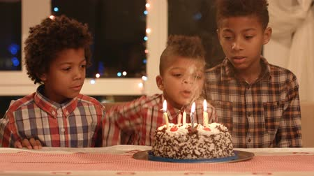 darkskinned : Kids blowing cakes candles out.