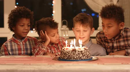 darkskinned : Group of kids beside cake.