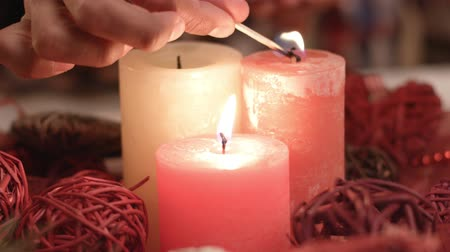 darkskinned : Childs hand lighting Christmas candles.
