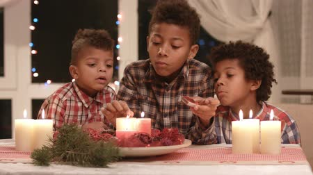 darkskinned : Black boys light Christmas candles.