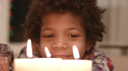 darkskinned : Smiling boy looks at candle.