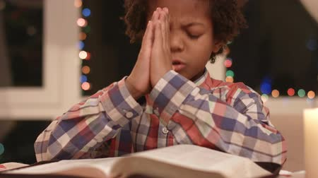 darkskinned : Mulatto boy praying.