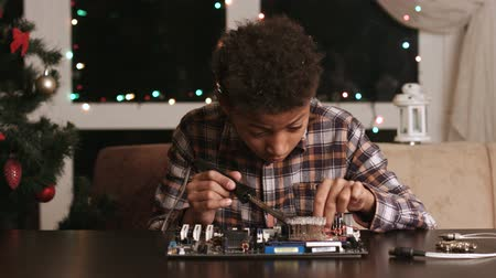 darkskinned : Afro boy fixing motherboard.
