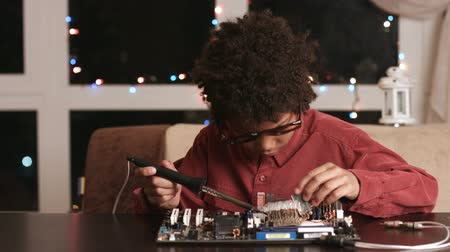 darkskinned : Surprised black boy fixing motherboard.