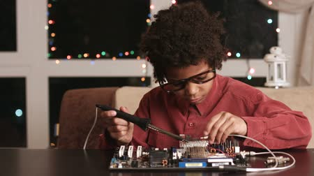 darkskinned : Darkskinned boy solders motherboard.