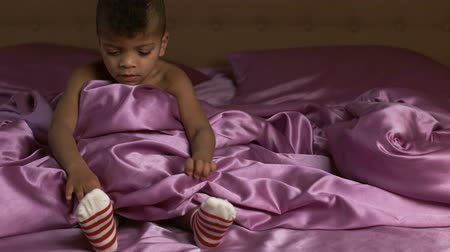 darkskinned : Boy moving feet on bed.