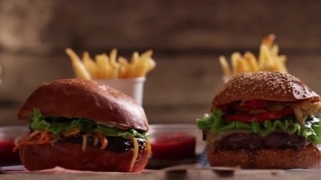 molho de tomate : Burgers with sauce and fries. Fast food with tomato sauce. Delicious-looking food on table. Choose your favorite. Stock Footage