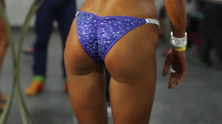 доля : Girls muscular back and butt. Sexy model in dark bikini. Result of correct time investment. Perfect tanned body.