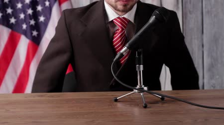 общественный : USA flag, man and microphone. Businessman speaking into the microphone. Time for motivational speech. Very important message. Стоковые видеозаписи
