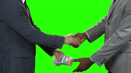 gesture pack : Businessmen with dollars shake hands. Handshake and money transfer. Monetary deal on green background. Roots of all evil. Stock Footage