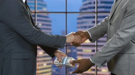 gesture pack : Businessmen with money shaking hands. Men in suits pass dollars. The risk is worth it. Company leaders made an agreement.