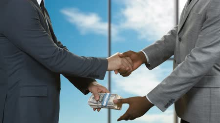 gesture pack : Men with cash shaking hands. Businessmen in suits pass money. Deal in company headquarters. Blue sky behind office window.