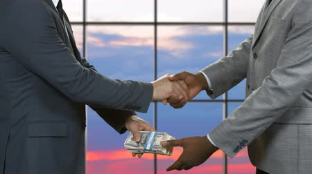 gesture pack : Handshake of men with dollars. Adult businessmen passing money. Financial deal on sunset background. Company found a new investor.