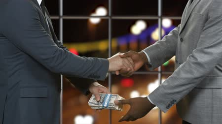 gesture pack : Men in suits shake hands. Businessmen passing dollar bundles. Financial deal on traffic background. Nighttime at the office.