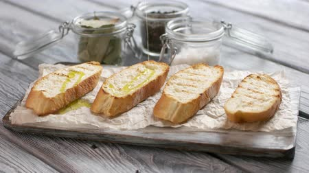 bruschetta : Liquid pours on bread slices. Pieces of baguette on paper. Olive oil for bruschetta. Preparation of simple snack.