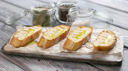 crostini : Spoon puts vegetables on toasts. Pieces of grilled bread. Bruschetta with baked vegetables. Traditional italian dish on table. Stock Footage