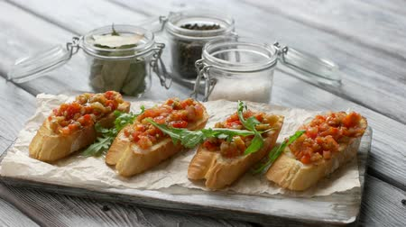 bruschetta : Herb falls on snack. Pieces of baguette with vegetables. Bruschetta with arugula leaves. Tasty meal on wooden table.