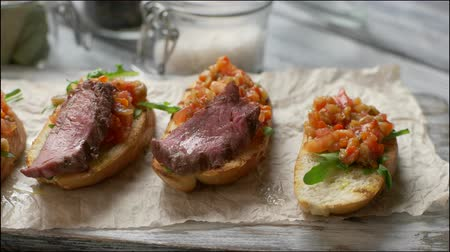 crostini : Tongs put meat on vegetables. Grilled toasts with vegetables. Bruschetta with juicy meat. Food for a gourmet. Stock Footage