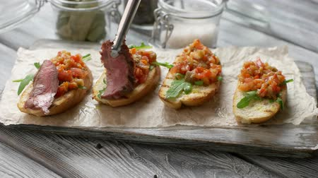 bruschetta : Tongs put meat on bread. Baguette slices with vegetables. Freshly cooked bruschetta. Traditional italian meal. Stock Footage