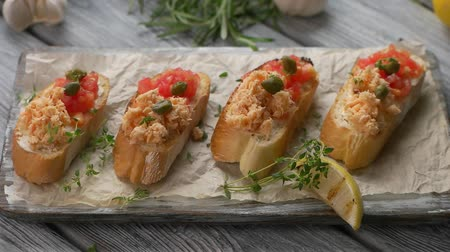 crostini : Herb slowly falls on sandwiches. Slices of baguette with fish. Bruschetta with salmon and tomatoes. Fresh and tasty appetizer.