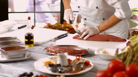 veal recipe : Man cuts meat with knife. Big piece of raw meat. Chef working with veal. Busy morning in the restaurant.