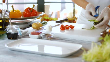peeler : Mans hands peel a cucumber. Cooking board on the table. Sliced cherry tomatoes. Busy morning of bistro chef.
