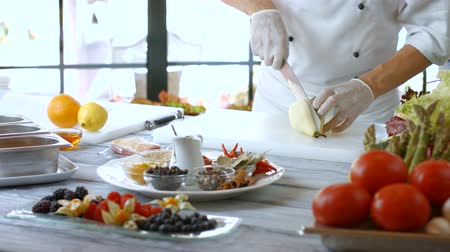 spices : Knife cuts pear in half. Pear on white cooking board. Cafe chef prepares fruit. Fresh ingredients only.