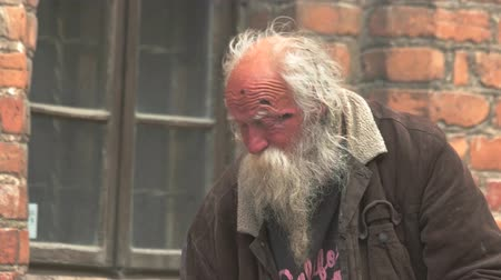 evsiz : Vilnius, Lithuania - 12.06.2016. Old homeless man with beard. Hobo in the street. Pain and despair. The most serious trouble. Stok Video