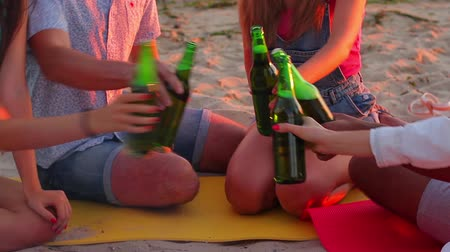 suécia : Young people clinking bottles. Company sits on the beach. Welcome to our humble party. Invite friends for a beer.