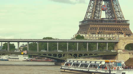bir hakeim bridge : Boats moving near Eiffel tower. Bir Hakeim bridge from distance. Popular tourist destination.