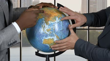 bizonyítani : Businessmen touching globe. Two men in suits. Conflict of interests. Prove youre right.