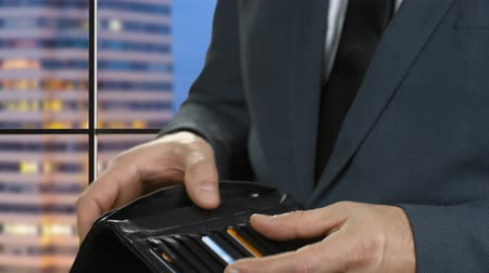 cüzdan : Hand of businessman holding dollar. Wallet of black color. Waiting for payday. Very close to trouble. Stok Video