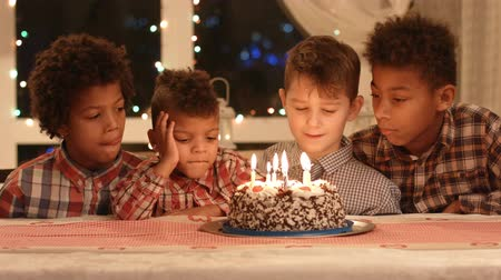 suécia : Kids near cake with candles. Boys sitting at the table. Celebrating our friends birthday. Only the best wishes.