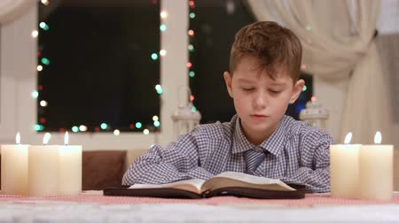 poezja : Boy is reading. Book and candles. Story about Christmas. Young mind opened for knowledge.